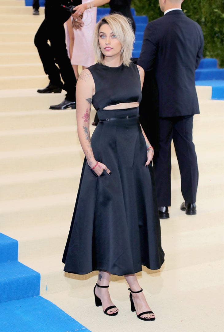 Paris Jackson wears a Calvin Klein By Appointment black duchess satin cut-out dress with tailored crossover bodice and satin strap waist detail.